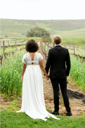 Bride and groom holding hands in the vineyard