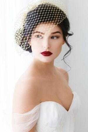 bride wearing a birdcage veil with red lipstick