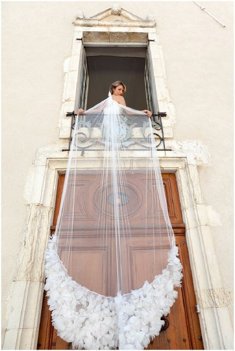 bridal standing with veil draped over balcony
