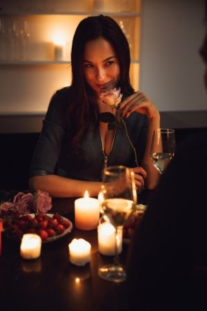 lady holding a rose at dinner table