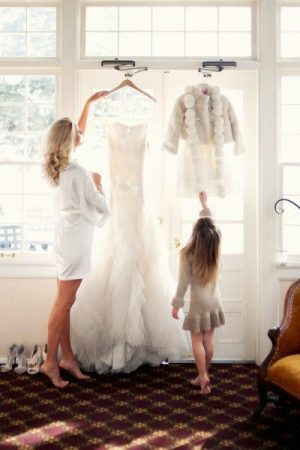 Flower girl and bride posing with dresses