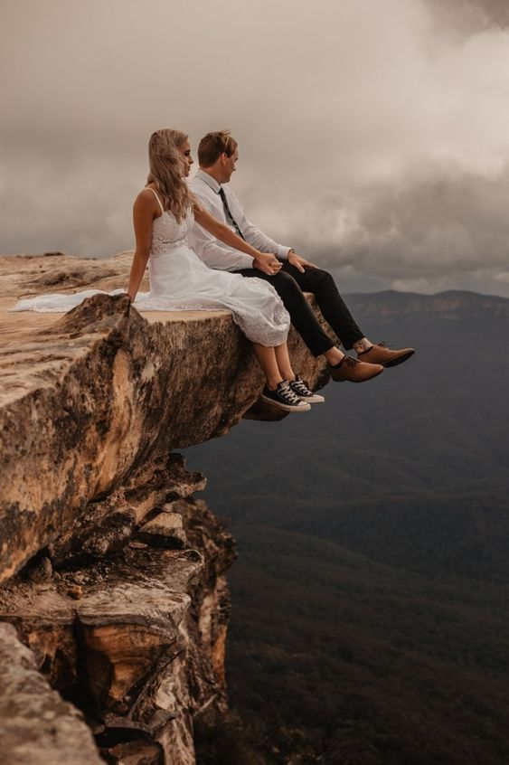 bride and groom sitting on the edge of a cliff