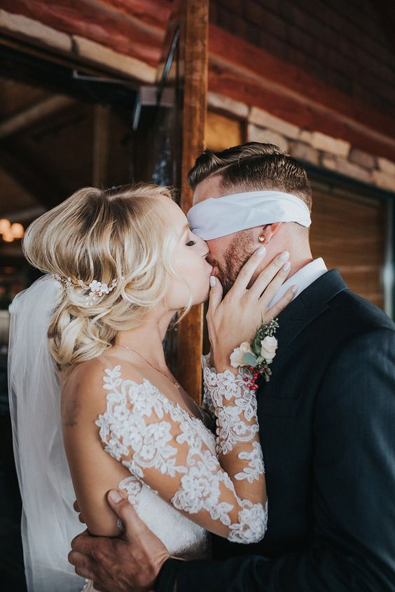 bride kissing her blindfolded groom