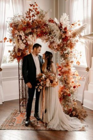 Brunette bride standing in front of backdrop