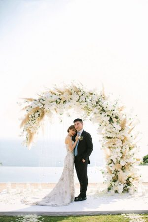 Couple in front of floral arch