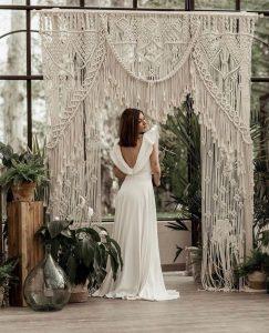 Brunette bride standing in front of macrame backdrop looking over her shoulder