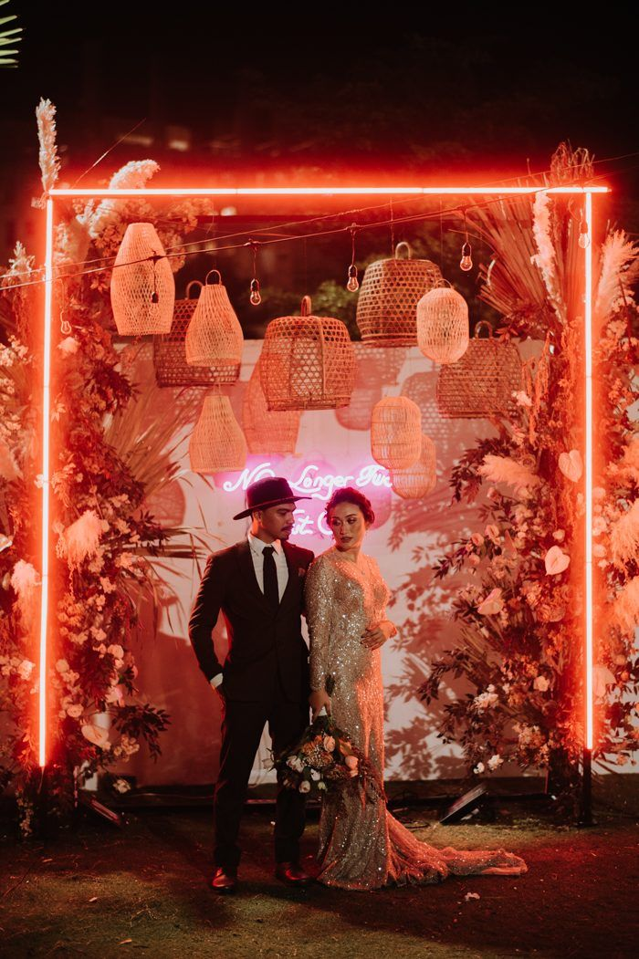 Bridal couple standing under neon arch
