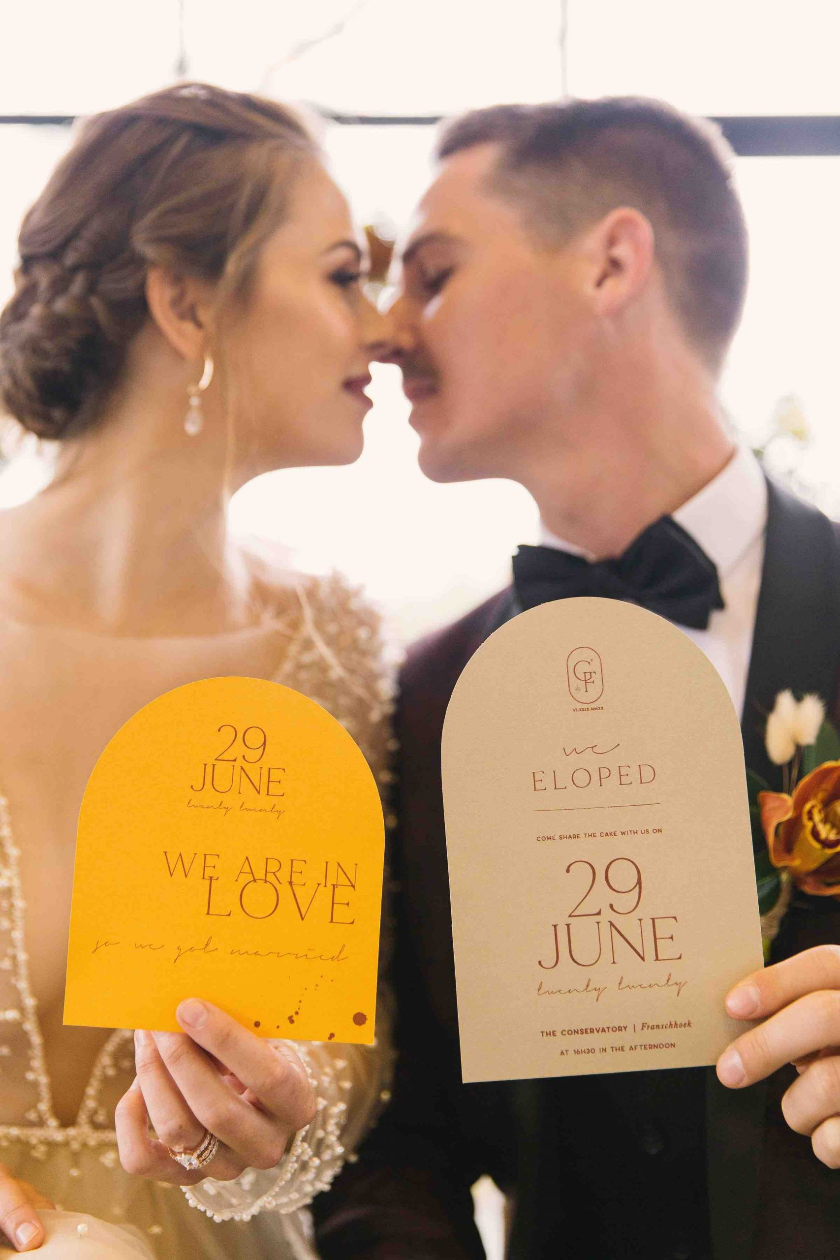 bridal couple holding wedding stationery