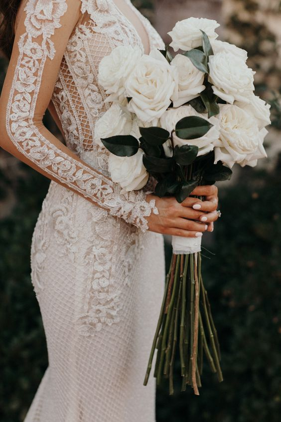 bride holding a bouquet of white roses