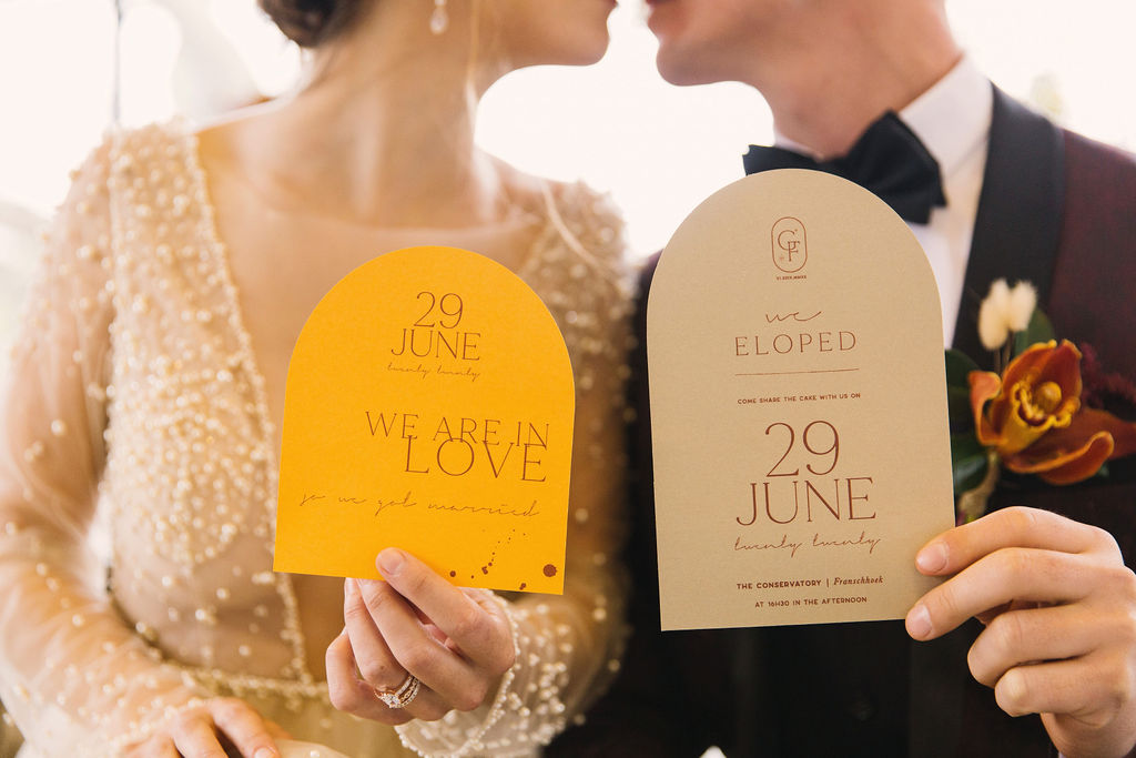bride and groom holding wedding stationery